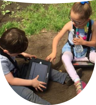 Two little kids on ground wearing their AAC devices